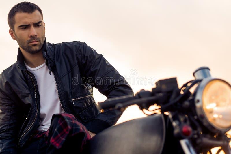 L'uomo brutale si siede sulla motocicletta di abitudine del corridore del caffè fotografie stock libere da diritti