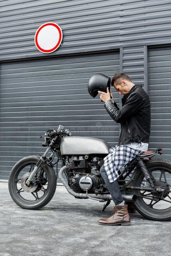 L'uomo brutale si siede sulla motocicletta di abitudine del corridore del caffè immagini stock