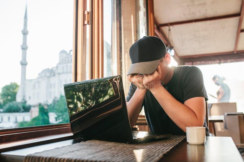 L'uomo in caffè si siede alla tavola con il computer vicino alla finestra ed al fronte nascosto a mano immagini stock
