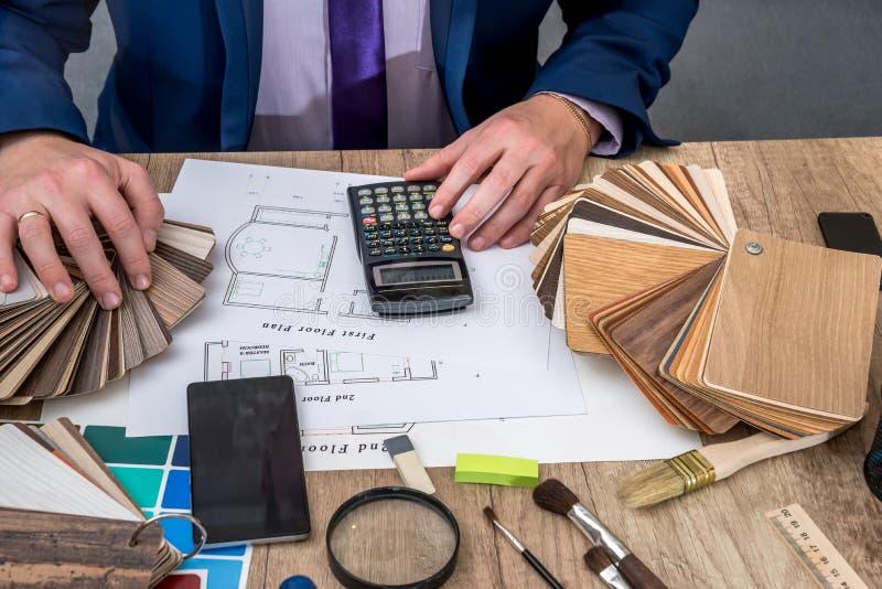 L'uomo calcola i materiali necessari per costruire fotografia stock