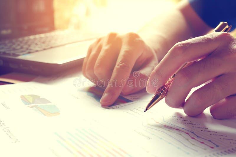L'uomo calcola il costo e le spese e computer portatile usando per i dati di ricerca immagini stock