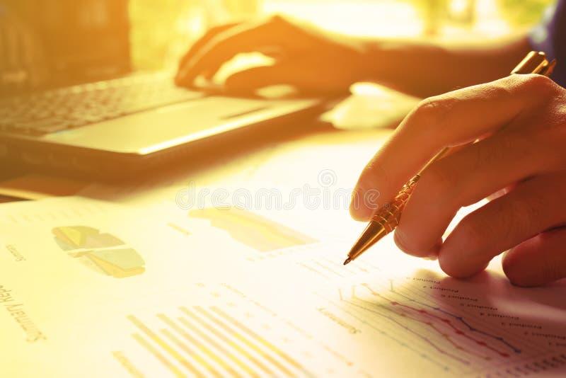 L'uomo calcola il costo e le spese e computer portatile usando per i dati di ricerca fotografie stock