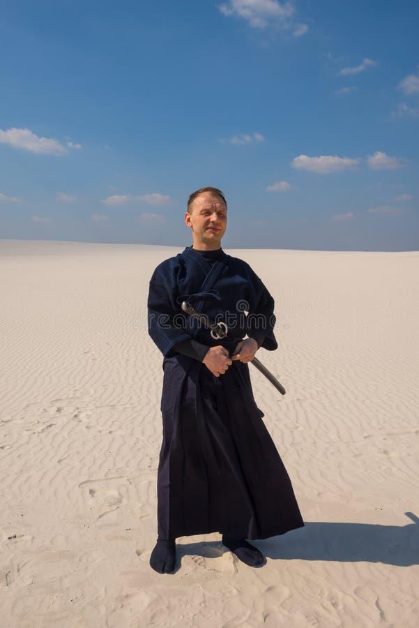 L'uomo calmo con il katana sta meditando in un deserto immagini stock libere da diritti