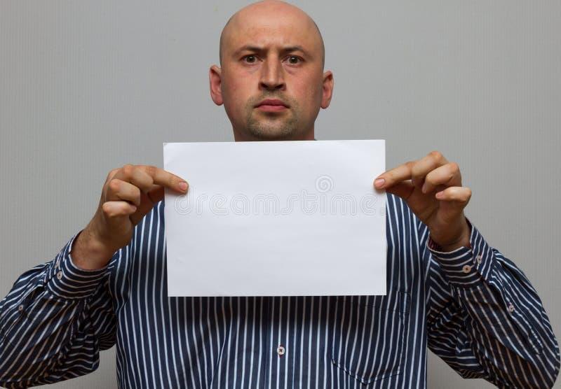 L'uomo calvo di affari sta posando con lo spazio in bianco della copia immagine stock