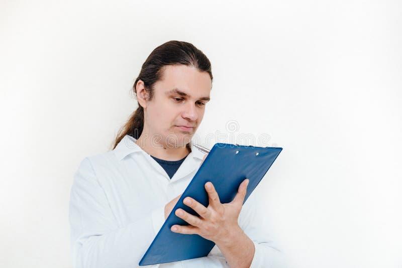 L'uomo in camice, in medico o in scienziato scrive alcune note sul cuscinetto di carta fotografia stock
