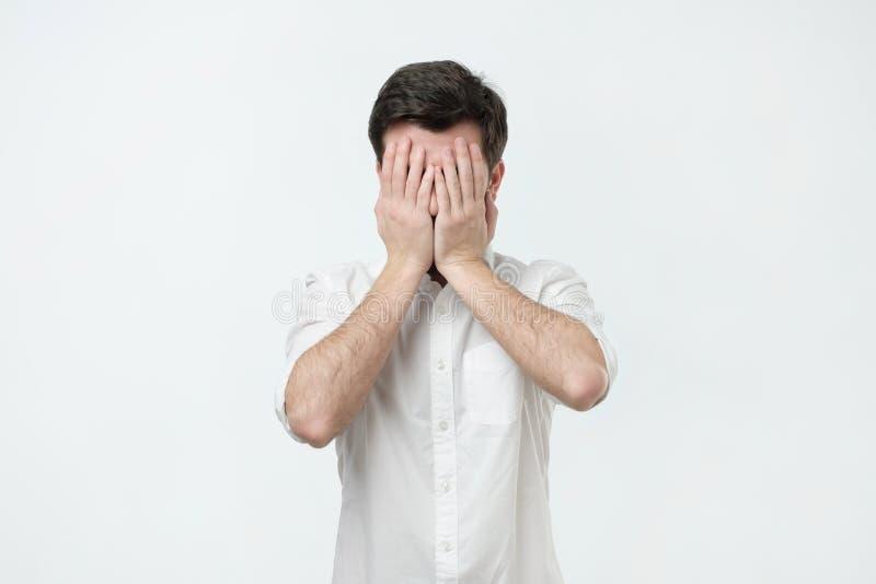 L'uomo in camicia bianca ha coperto il suo fronte di sue mani fotografie stock