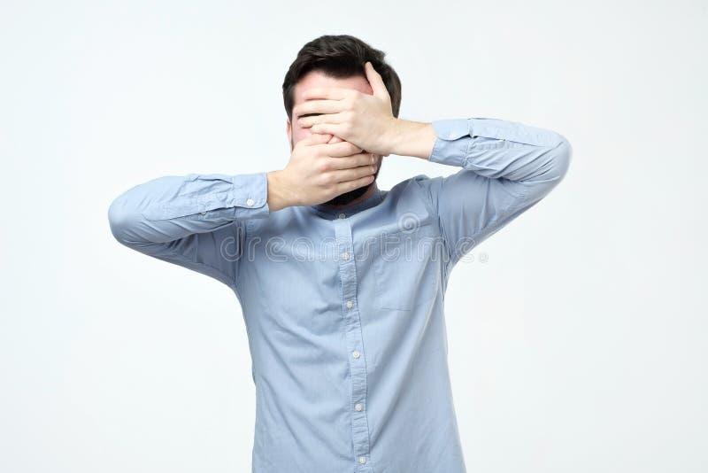 L'uomo in camicia blu ha coperto il suo fronte di sue mani immagine stock