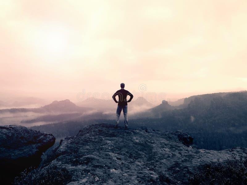 L'uomo in camicia ed i jeans sul picco dell'arenaria oscillano la sorveglianza nella valle nebbiosa e nebbiosa Bello momento, mir immagini stock