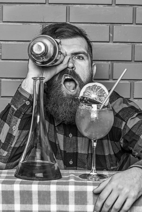 L'uomo in camicia a quadretti tiene l'agitatore davanti all'occhio, fondo del muro di mattoni Barista e concetto dei cocktail Bar immagine stock