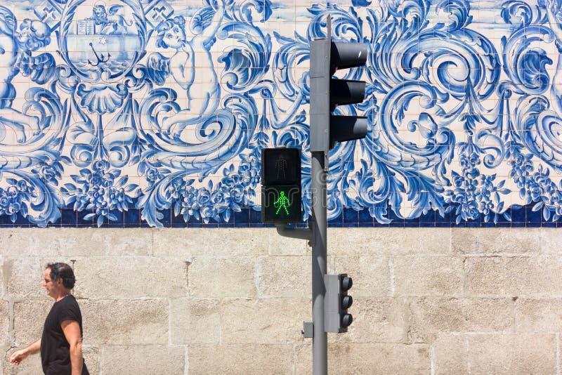 L'uomo cammina dopo il azulejo di bianco e blu delle mattonelle sulla chiesa di Carmo a Oporto, Portogallo fotografia stock libera da diritti