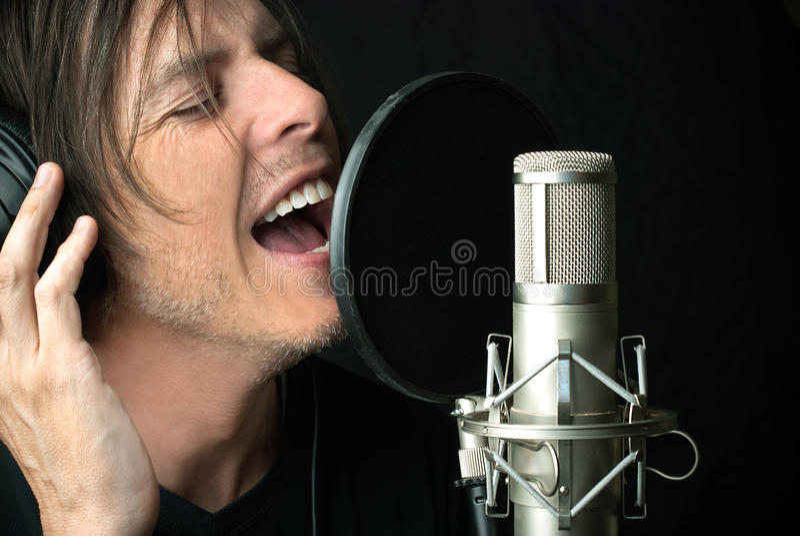 L'uomo canta nel microfono di condensatore fotografia stock