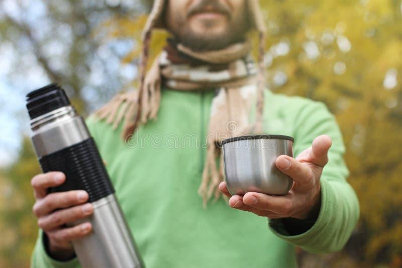 L'uomo in cappello e sciarpa tricottati, con il sorriso offre la bevanda calda - tè o caffè dal termos, vista frontale fotografie stock libere da diritti