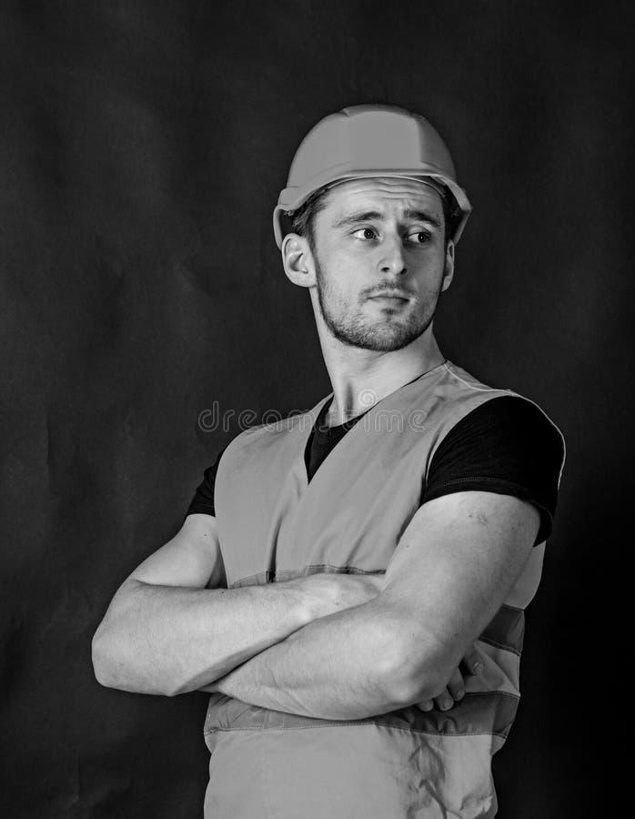 L'uomo in casco, armi della tenuta del casco ha attraversato sul petto, fondo nero Lavoratore, appaltatore, costruttore sul front fotografia stock libera da diritti