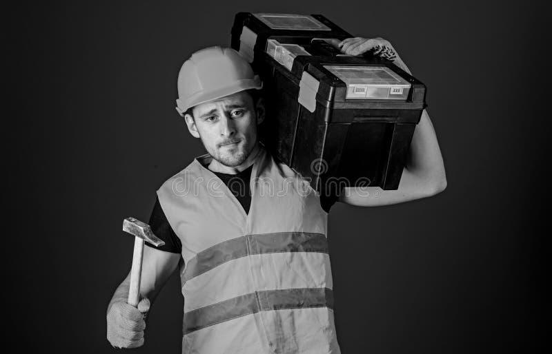 L'uomo in casco, casco porta la cassetta portautensili e le tenute martellano, fondo blu Lavoratore, riparatore, riparatore, cost fotografia stock libera da diritti