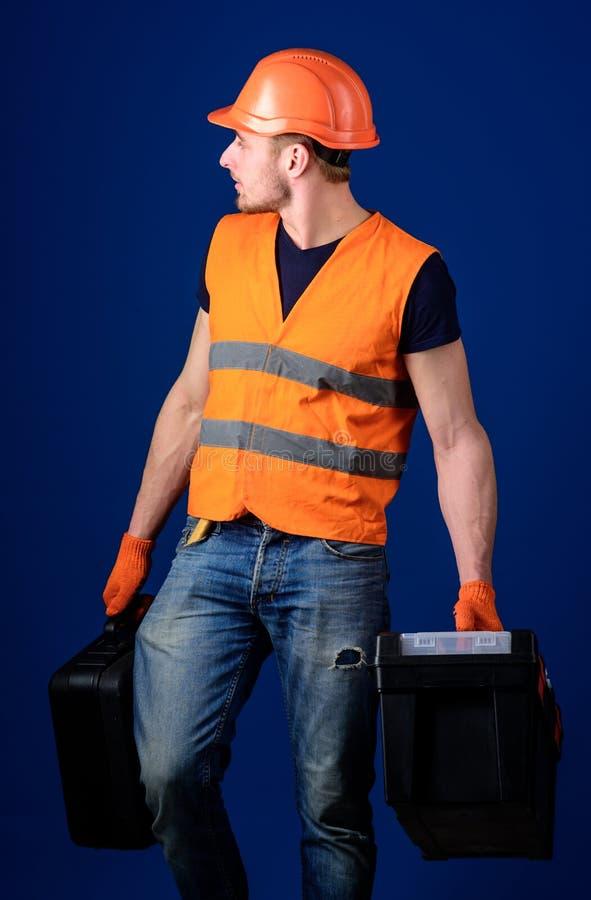 L'uomo in casco, casco tiene la cassetta portautensili e la valigia con gli strumenti, fondo blu Concetto fornito del riparatore  immagini stock