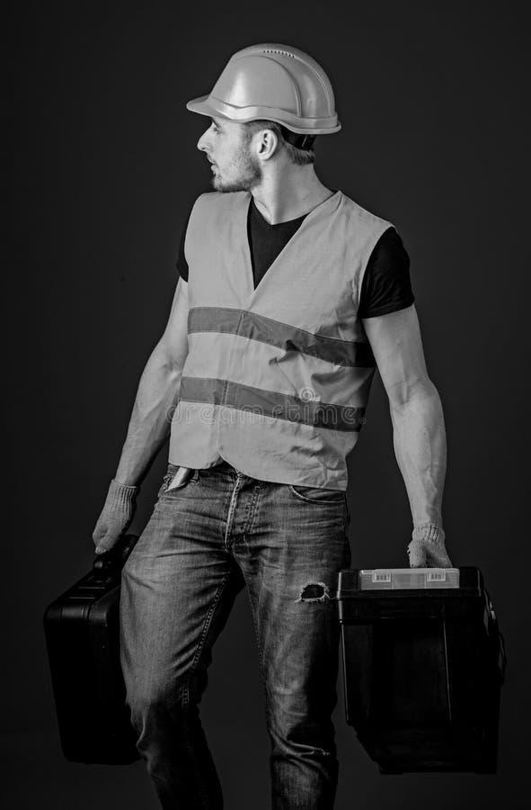 L'uomo in casco, casco tiene la cassetta portautensili e la valigia con gli strumenti, fondo blu Concetto fornito del riparatore  fotografie stock