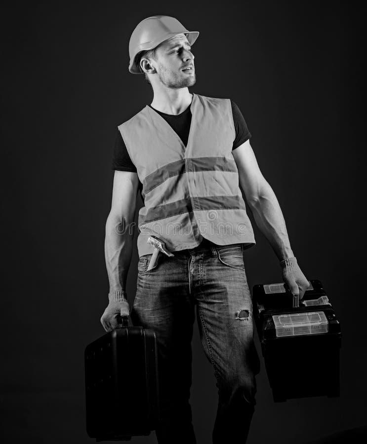 L'uomo in casco, casco tiene la cassetta portautensili e la valigia con gli strumenti, fondo blu Il tuttofare, riparatore sul fro fotografia stock libera da diritti