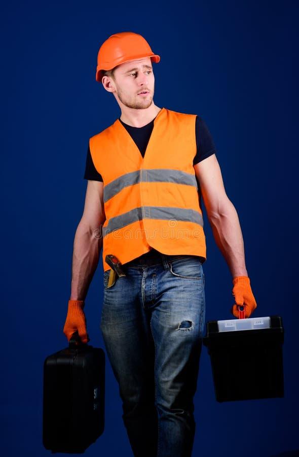 L'uomo in casco, casco tiene la cassetta portautensili e la valigia con gli strumenti, fondo blu Tuttofare, riparatore sul fronte immagini stock