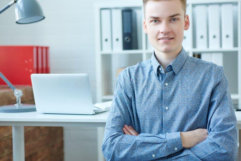 L'uomo caucasico sorridente di affari dei giovani sta esaminando la macchina fotografica, sedentesi davanti al suo posto di lavor immagini stock
