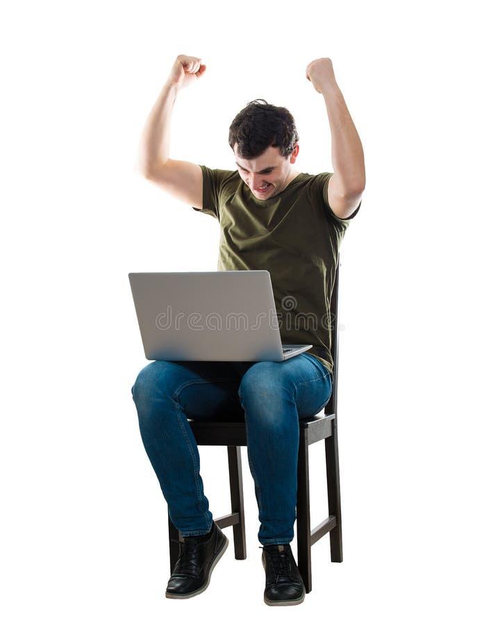 L'uomo celebra il successo facendo uso del computer portatile immagine stock