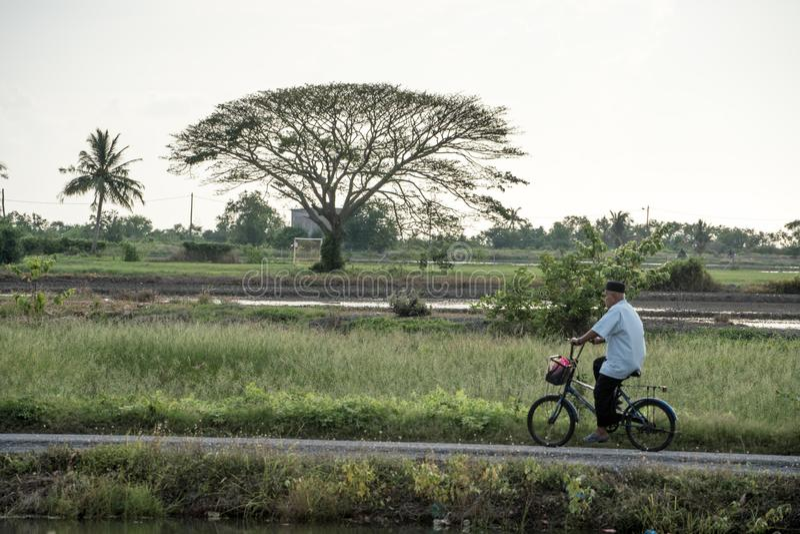 L'uomo che cicla attraverso il villaggio immagine stock libera da diritti