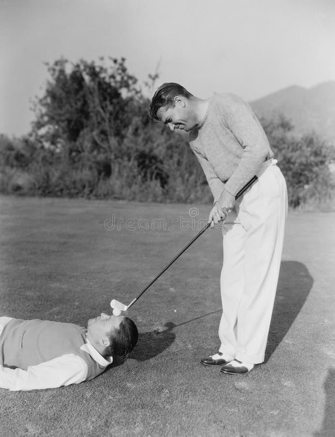 L'uomo che colpisce la palla da golf sopra equipaggia la fronte (tutte le persone rappresentate non sono vivente più lungo e ness immagine stock