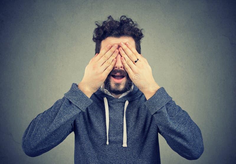 L'uomo che copre i suoi occhi consegna il fondo grigio fotografie stock libere da diritti