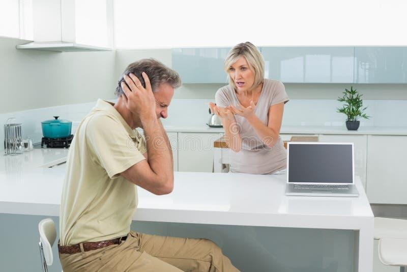 L'uomo che copre le sue orecchie come donna discute in cucina immagine stock