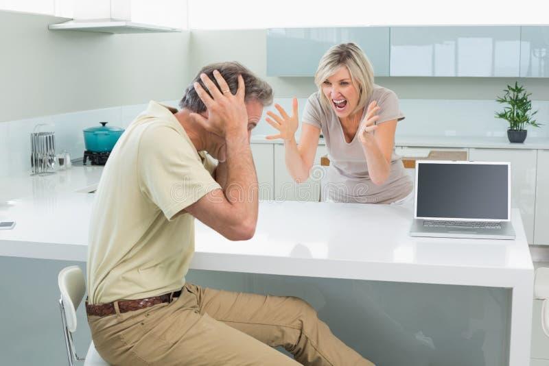 L'uomo che copre le sue orecchie come donna discute in cucina fotografie stock libere da diritti