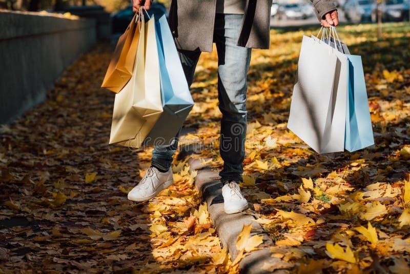 L'uomo che di divertimento di autunno i sacchetti della spesa cadono lascia il marciapiede immagine stock libera da diritti