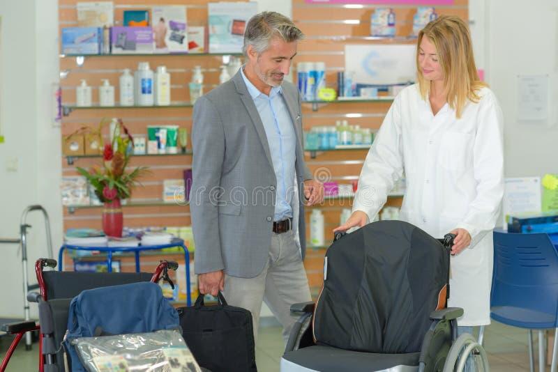 L'uomo che esamina la sedia a rotelle nei rifornimenti medici compera immagini stock