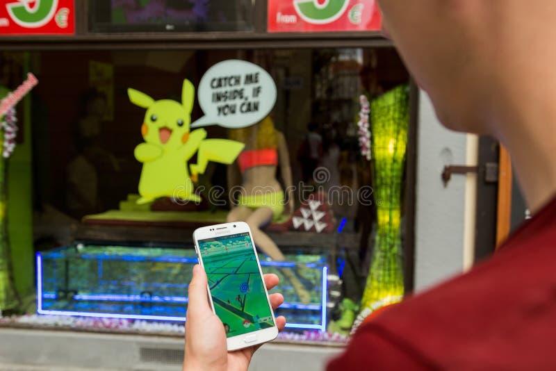 L'uomo che gioca Pokemon va all'aperto immagini stock
