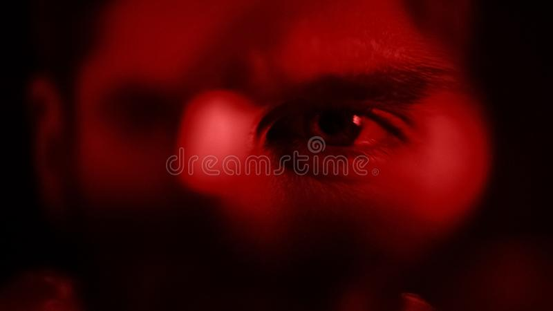 L'uomo che guarda attraverso il primo piano della lente d'ingrandimento, esperto criminale analizza, cerca fotografia stock libera da diritti