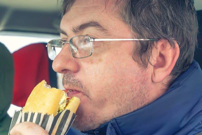 L'uomo che indossa occhiali mangia sandwich immagini stock libere da diritti