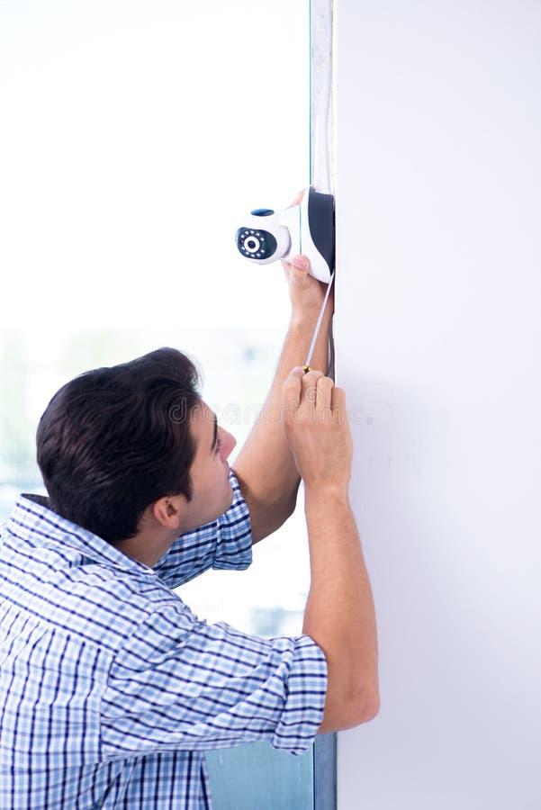 L'uomo che installa le macchine fotografiche del cctv di sorveglianza a casa immagine stock libera da diritti