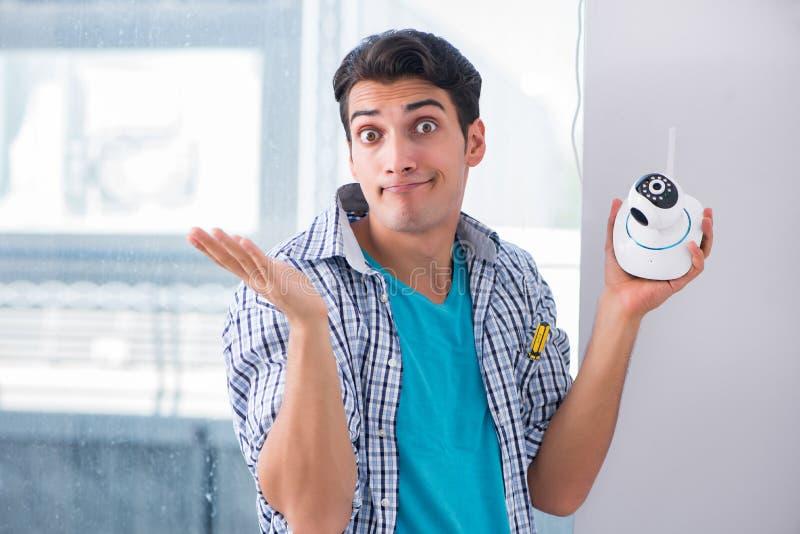 L'uomo che installa le macchine fotografiche del cctv di sorveglianza a casa immagini stock libere da diritti
