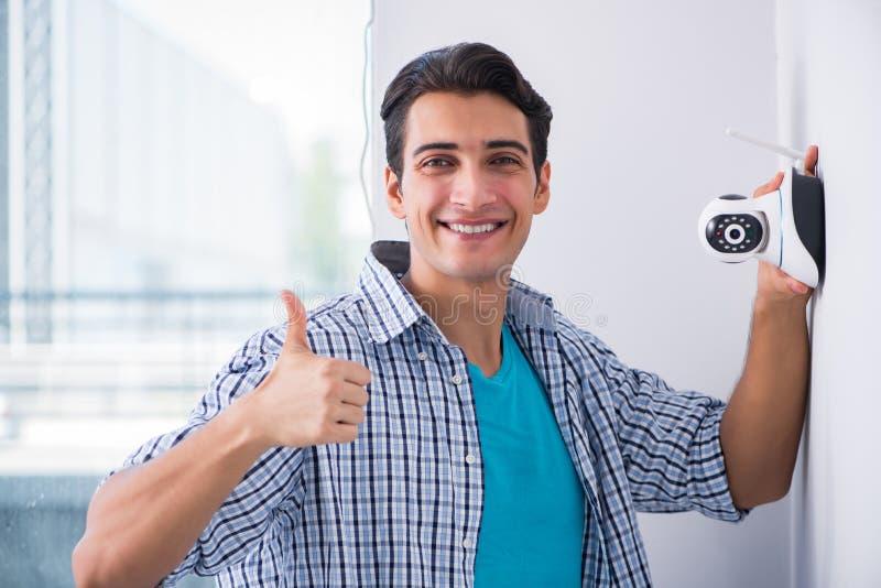 L'uomo che installa le macchine fotografiche del cctv di sorveglianza a casa fotografia stock