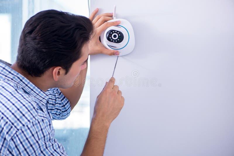 L'uomo che installa le macchine fotografiche del cctv di sorveglianza a casa immagine stock