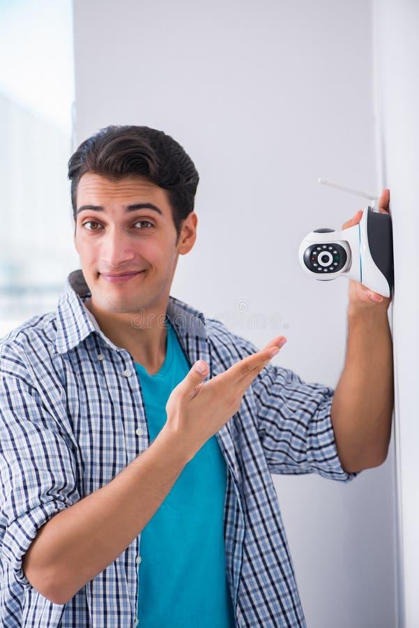 L'uomo che installa le macchine fotografiche del cctv di sorveglianza a casa immagini stock
