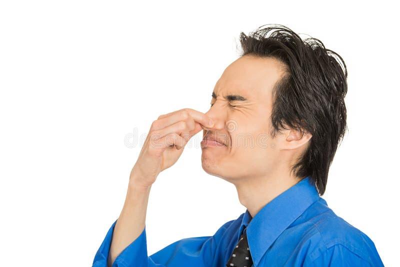 L'uomo che la repulsione sul suo fronte pizzica il suo naso, qualcosa puzza il cattivo odore immagine stock libera da diritti
