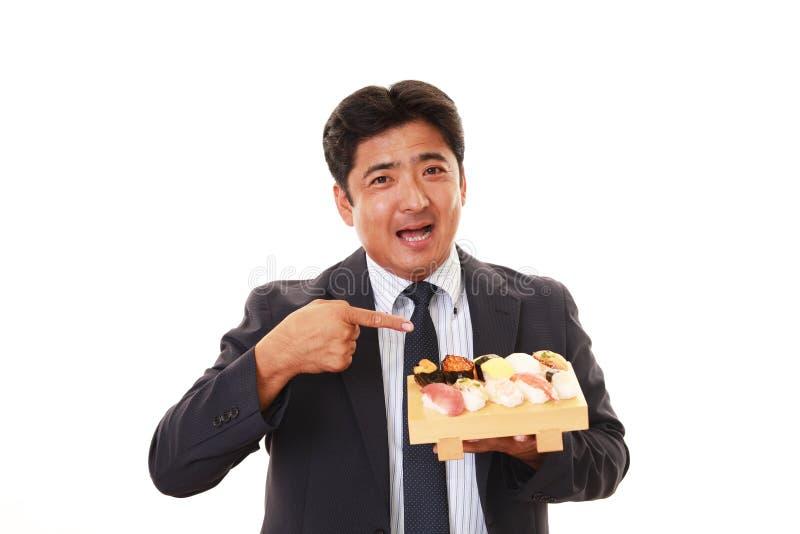 L'uomo che mangia i sushi fotografie stock