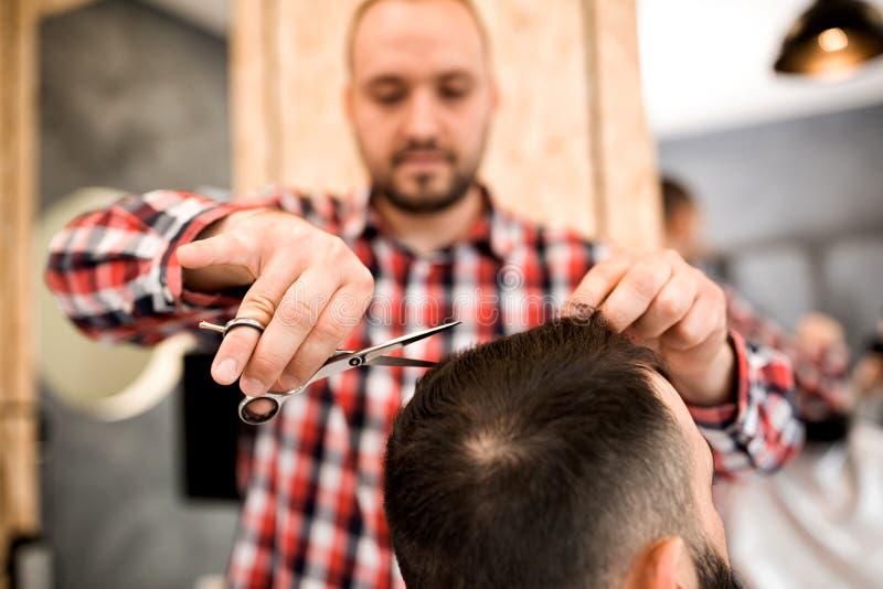 L'uomo che ottiene i suoi capelli ha tagliato al negozio di barbiere fotografia stock