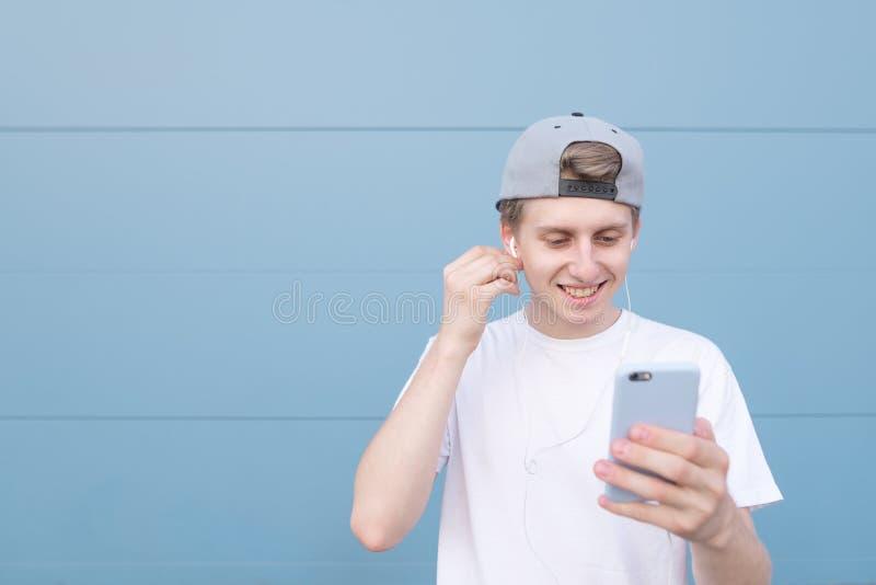 L'uomo che porta una maglietta bianca ascolta musica in cuffie ed utilizza uno smartphone su un fondo pastello blu fotografia stock