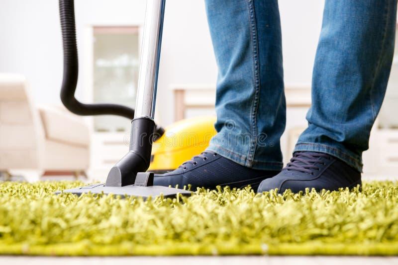 L'uomo che pulisce il tappeto del pavimento con una fine dell'aspirapolvere su immagini stock libere da diritti