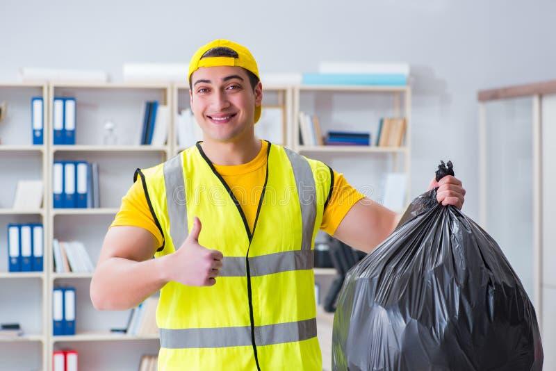 L'uomo che pulisce l'ufficio e che tiene la borsa di immondizia fotografia stock libera da diritti