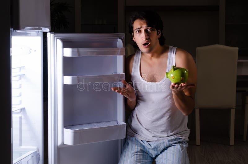 L'uomo che rompe dieta alla notte vicino al frigorifero immagini stock libere da diritti