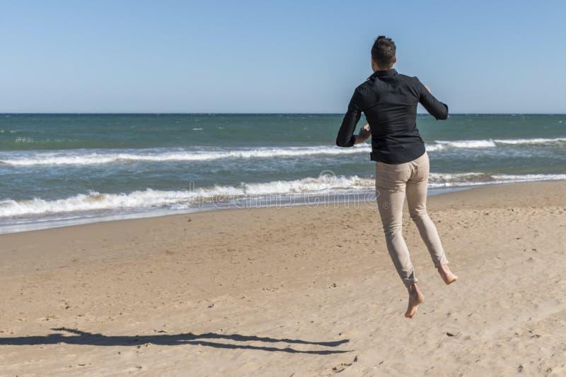 L'uomo che salta felicemente sulla spiaggia immagine stock libera da diritti