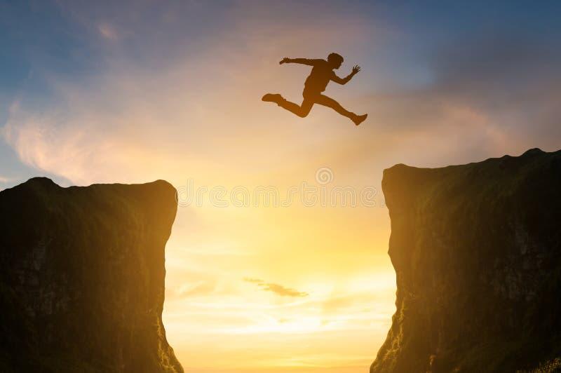 L'uomo che salta sopra la scogliera, siluetta immagine stock