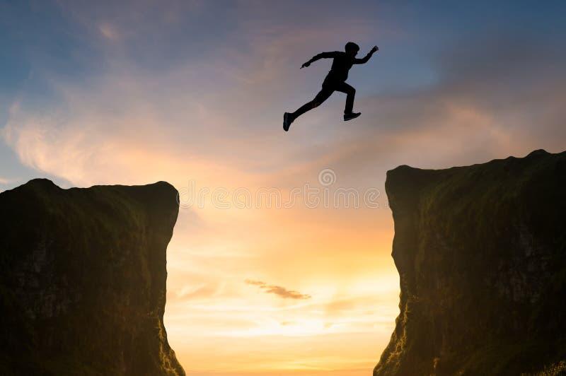 L'uomo che salta sopra la scogliera, siluetta fotografie stock