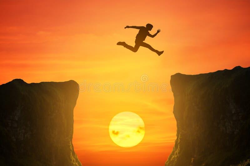 L'uomo che salta sopra la scogliera, siluetta immagine stock libera da diritti